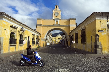 Antigua, Guatemala - January 25, 2009: Girl biking in Antigua. 5th Avenue North, Santa Catalina Arch and La Merced Cathedral in the background . Taken winter afternoon. Editorial