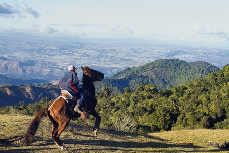 guatemala: Guatemala City, Guatemala, USA Boy on the horse on the tourist route to Pacaya Volcano. Guatemala City in the background. Seen winter time late afternoon Editorial