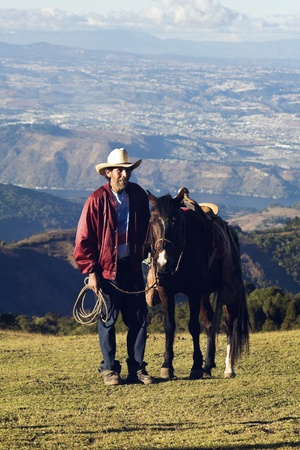 cowboy on horse: Guatemala City, Guatemala, USA January 25, 2009 Man with a horse on the tourist route to Pacaya Volcano. Guatemala City in the background. Seen winter time late afternoon Editorial