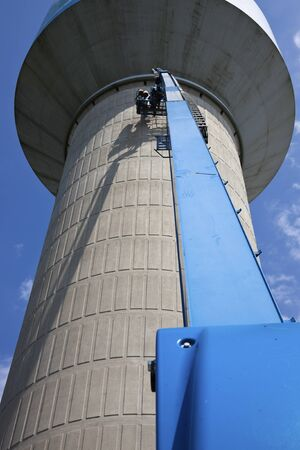 Lift used in the telecom work - crew installing wireless antennas on the concrete water tower photo