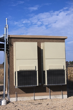 Equipment shelter on the cellular site. GPS antenna on the left. Editorial