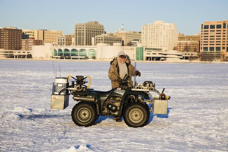 Fisherman with his quad on the frozen Lake Monona in Madison, Wisconsin. Seen March morning. Madison, Wisconsin, USA March 04, 2010: