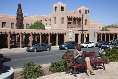 adobe pueblo: Woman sitting on the bench by Cathedral Place. Museum of Contemporary Native Arts accross the street.  The museum occupies the historic Santa Fe Federal Building listed in National Register of Historic Places. Seen during fall morning. Santa Fe, New Mexic