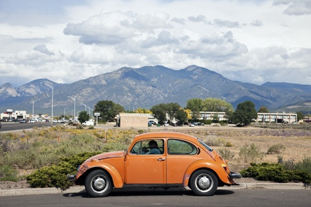 parked: Old, Orange Volkswagen Beetle seen in Taos, New Mexico with Taos Mountains in the background. Fall afternoon. The Beetle is the most produced car in the world with over 21 million automobiles sold. The production ran from 1938 to 2003. Taos, New Mexico, U