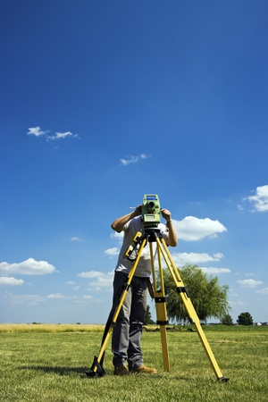 surveyor: Behind Theodolite - land surveying in rural area.