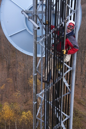 construction crew: Tower climber inside the guyed tower measuring with the tape the elevation of the dish antenna