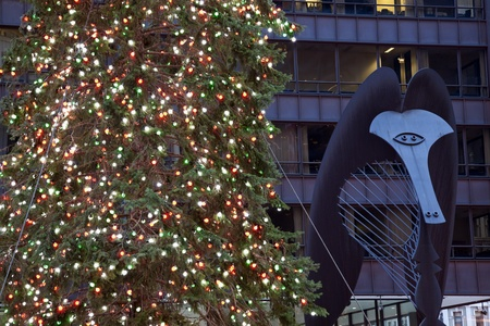 Chicago, Illinois, USA - December 05, 2009: Christmas tree and the unnamed sculpture created by Pablo Picasso in the background. Seen winter evening. The sculpture is called Chicago Picasso or The Picasso. Completed in 1966, was set in Daley Plaza in down