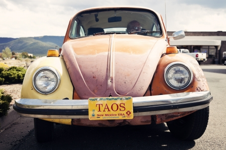 Taos, New Mexico, USA - October 3, 2011: Old, Orange Volkswagen Beetle seen in Taos, New Mexico with Taos word on New Mexico plates. Taos Mountains in the background. Fall afternoon. The Beetle is the most produced car in the world with over 21 million au