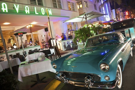 Miami Beach, Florida, USA December 29, 2011 First generation (1955–1957) Ford Thunderbird parked in front of the restaurant in Hotel Avalon in Miami Beach, Florida. Seen evening time. Hotel Avalon is located by Ocean Drive and represents Art Deco archit