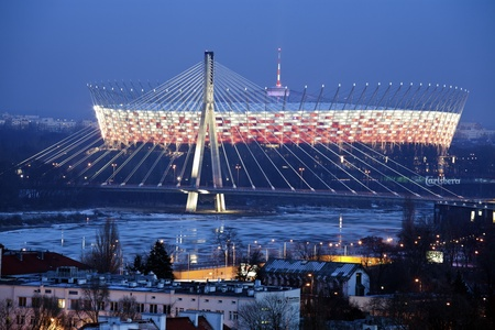 Warsaw, Poland - January 29, 2012 The National Stadium in Warsaw, Poland. The stadium opened January 29, 2012. Its going to host the opening game during UEFA Euro 2012. The capacity of the object is 58500. Seen winter evening with Swietokrzyski Bridge an Redakční