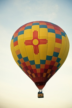 albuquerque: Albuquerque, New Mexico, USA - October 2, 2011: Hot Air Baloon Fiesta in Albuquerque, New Mexico. Hot air baloon with New Mexico Zia Sun symbol ascending during the sunrise. Seen with clear sky in the background.