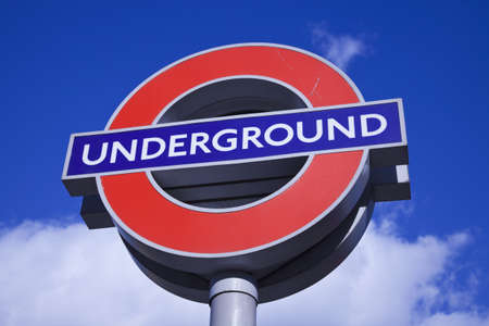 approximate: London, England - February 19, 2012 London Underground sign seen in Kings Cross area. Approximate daily usage of London metro system is 3 million people. London Underground started operations in 1863. Sign seen during winter day against blue sky with clo Editorial