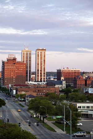 settled: Peoria, Illinois, USA - April 17, 2012 Peoria skyline at sunset. Seen during spring afternoon with the City Hall building and Twin Towers. Peoria was settled in 1680 and in 2010 the population was 115000.