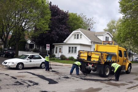pot hole: Milwaukee, Wisconsin, USA - May 09, 2012 Department of Public Works crew (three workers and driver) fixing the holes in the road. Person from City of Milwaukee driving by. Seen spring morning of May 2012.