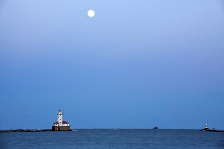 lake michigan lighthouse: Luna llena que se levanta sobre el lago Michigan y el faro de Chicago