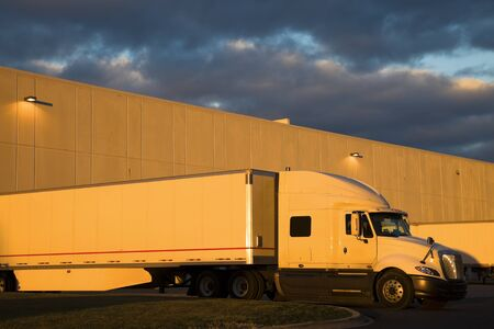 White Semi Truck in the loading dock. Seen during sunset with the warm light and dramatic sky. photo