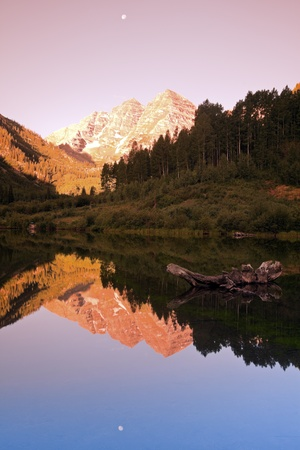 Maroon Bells - sunrise in the mountains. Full moon reflected. photo