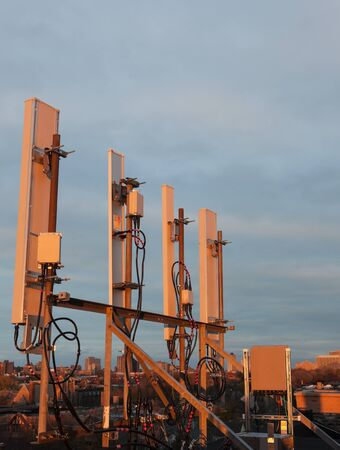 Cellular antennas on the roof in the warm sunset light
