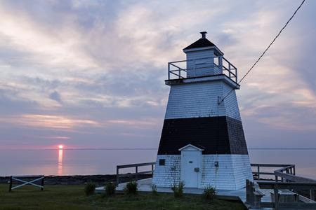 nova: Margaretsville Lighthouse at sunset. Nova Scotia, Canada. Stock Photo