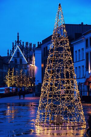flemish region: Christmas tree on Veemarkt in Mechelen. City Hall in the back. Mechelen, Flemish Region, Belgium