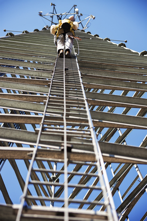Climber ascending cell phone tower. Wisconsin, USA.