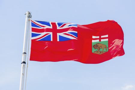 Manitoba flag against blue sky. Winnipeg, Manitoba, Canada.