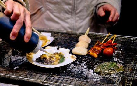 grilled abalone and other seafood cooking over the barbecue grill at fish market in Japan Stock Photo