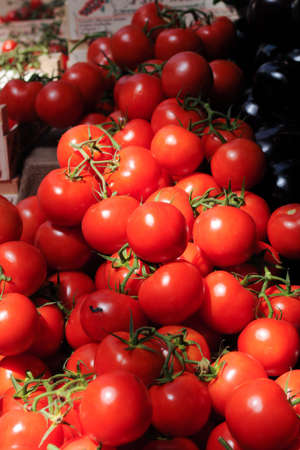 Lots of fresh bright red tomatoes at a market. photo