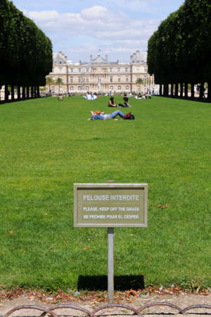contradict: Keep Off The Grass sign at a park, with people in the background lying on the grass, ignoring the sign. Stock Photo