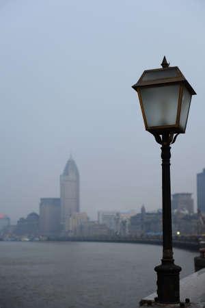 Un-lit classical street light in Shanghai harborside at dusk. photo