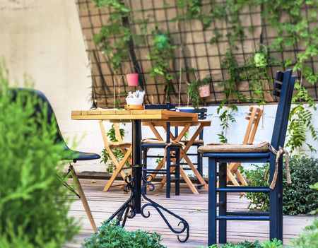 Wooden table and black chair in the cafe garden
