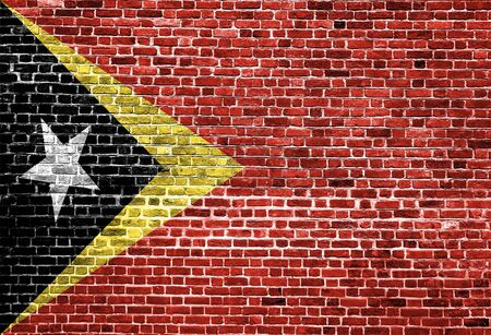 Flag of East Timor painted on brick wall, background texture