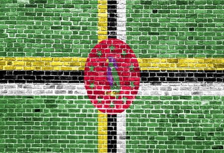Flag of Dominica painted on brick wall, background texture