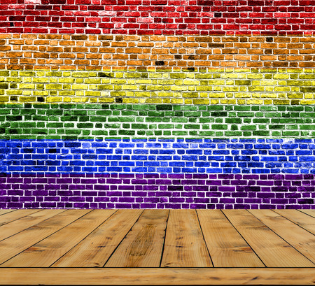 homosexuales: LGBT flag painted on brick wall with wooden floor