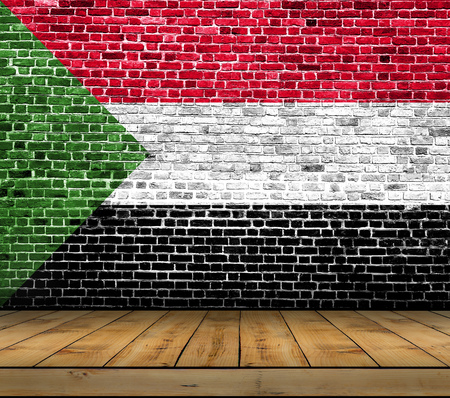 Sudan flag painted on brick wall with wooden floor