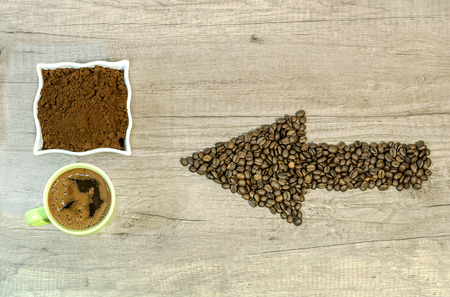 Arrow from the coffee beans with a cup of fresh ground coffee on wooden background Reklamní fotografie
