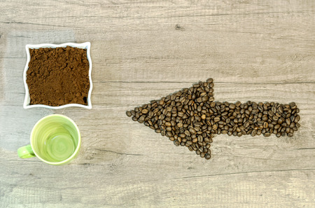 Arrow from the coffee beans with a cup of fresh ground coffee and empty cup on wooden background Reklamní fotografie