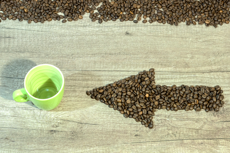 Arrow from the coffee beans with a cup of drink on wooden background