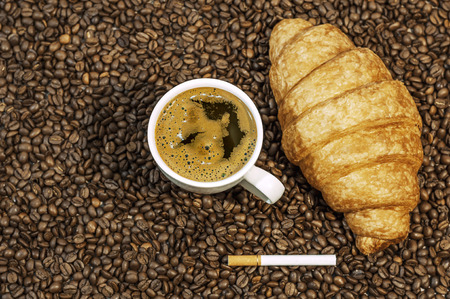 Coffee bean background with cup of fresh hot coffee, cigar and croissant on kitchen table