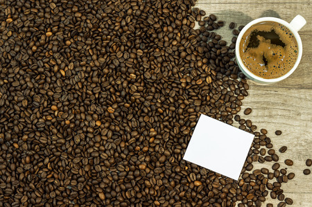 Coffee bean background with cup of fresh hot coffee and space for text on kitchen table