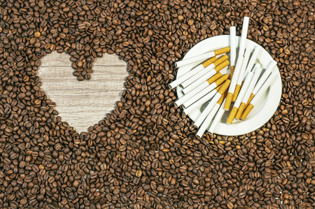 Coffee bean background with heart and many cigars on white plate on kitchen table
