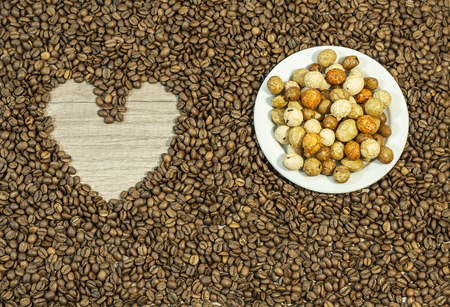 Coffee bean background with heart and plate full of various peanut