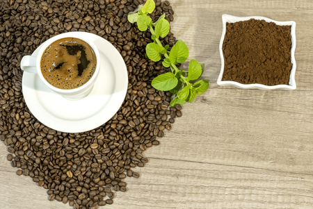 Cup of fresh coffee, coffee beans,  fresh ground coffee and mint tea flovers on wooden table Reklamní fotografie