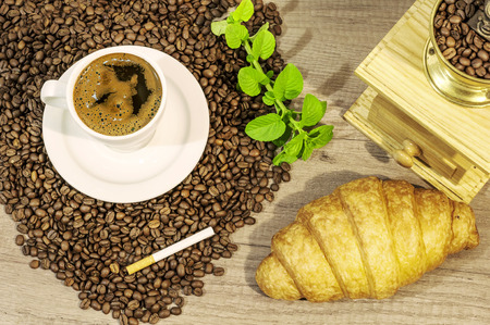 Cup of fresh coffee, coffee beans, croissant, coffee grinder, cigar and mint tea flovers on wooden table
