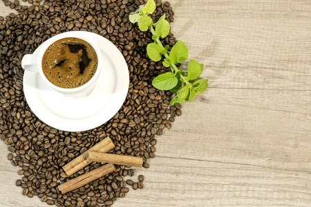 Cup of fresh coffee, coffee beans, cinnamon and mint tea flowers on wooden table