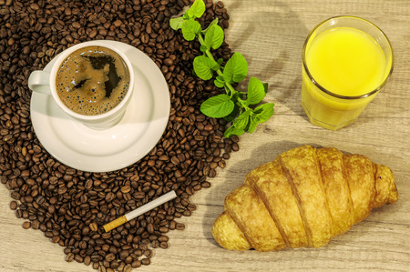 Cup of fresh coffee, coffee beans, croissant, juice and mint tea flovers on wooden table