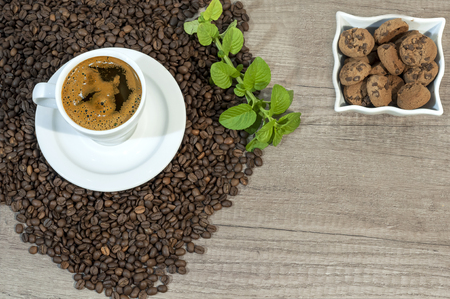 Cup of fresh coffee, coffee beans, cookies with cocholate and mint tea flovers on wooden table
