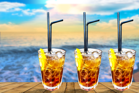 Three Cuba libre exotic tasty cocktail with beautiful sunset background