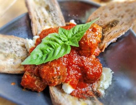 Meatballs in a plate with bread on table