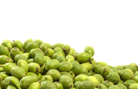 A lot green young walnuts in husks on white background Stock Photo
